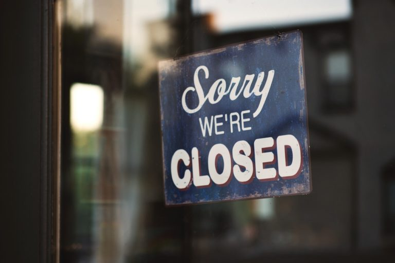 'Sorry we're closed' sign displayed outside an empty shop