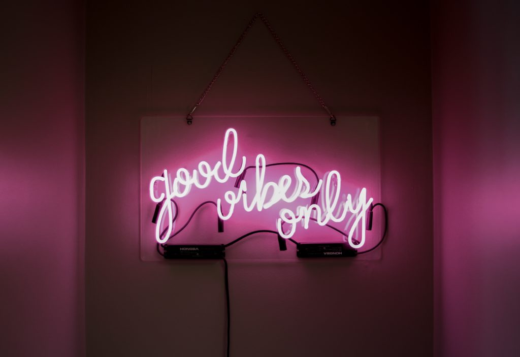 neon sign saying 'good vibes only' in a nightclub