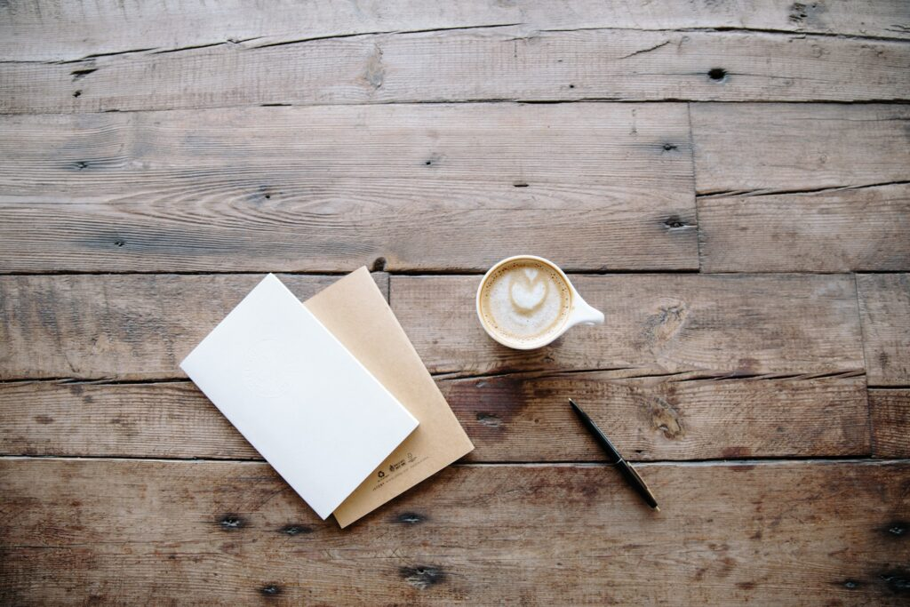 Coffee on a wooden table next to a pen and blank letter