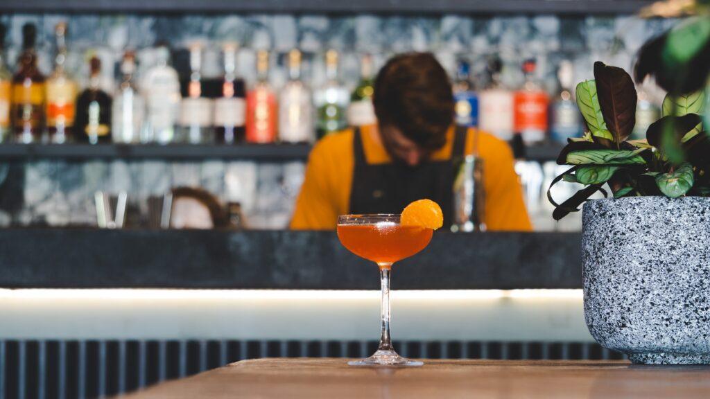 Bartender standing behind a drink with orange garnish