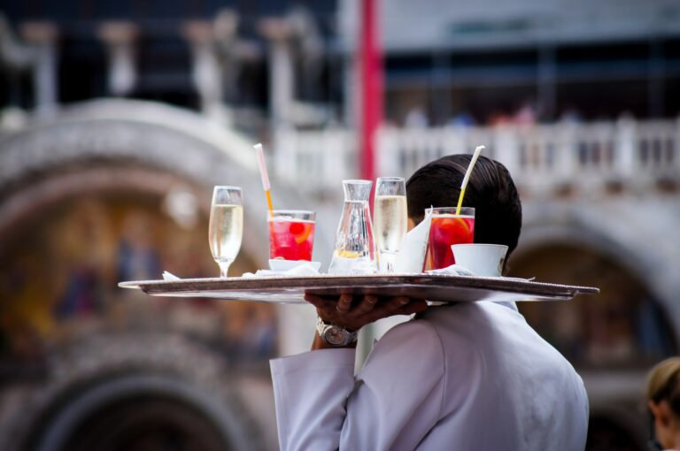waiter carrying a tray full of drinks and cocktails